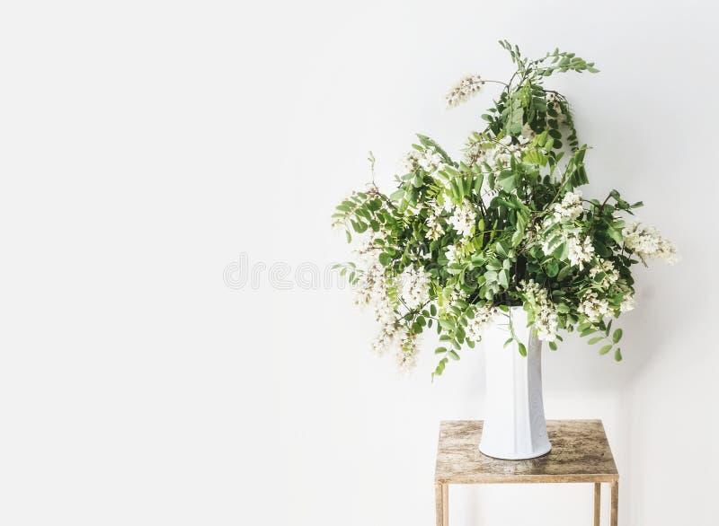 Kwiat wiązka z okwitnięciem akacja rozgałęzia się w wazie przy biel ścianą Prosty Wewnętrzny projekt i pomysły zdjęcia royalty free