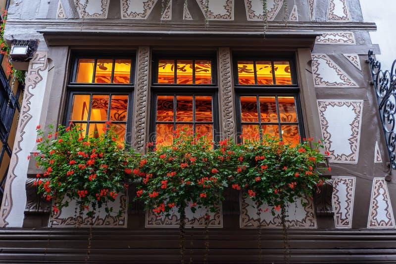 Kwiatu łóżko kwiaty na nadokiennej fasadzie stary dom w Europe Francja zdjęcie stock