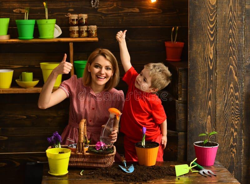 Kwiatu pojęcie Szczęśliwy rodzinny uśmiech z aprobatami w kwiatu sklepie Macierzysty i mały syn rośliny kwiat w garnku codzienny obrazy stock