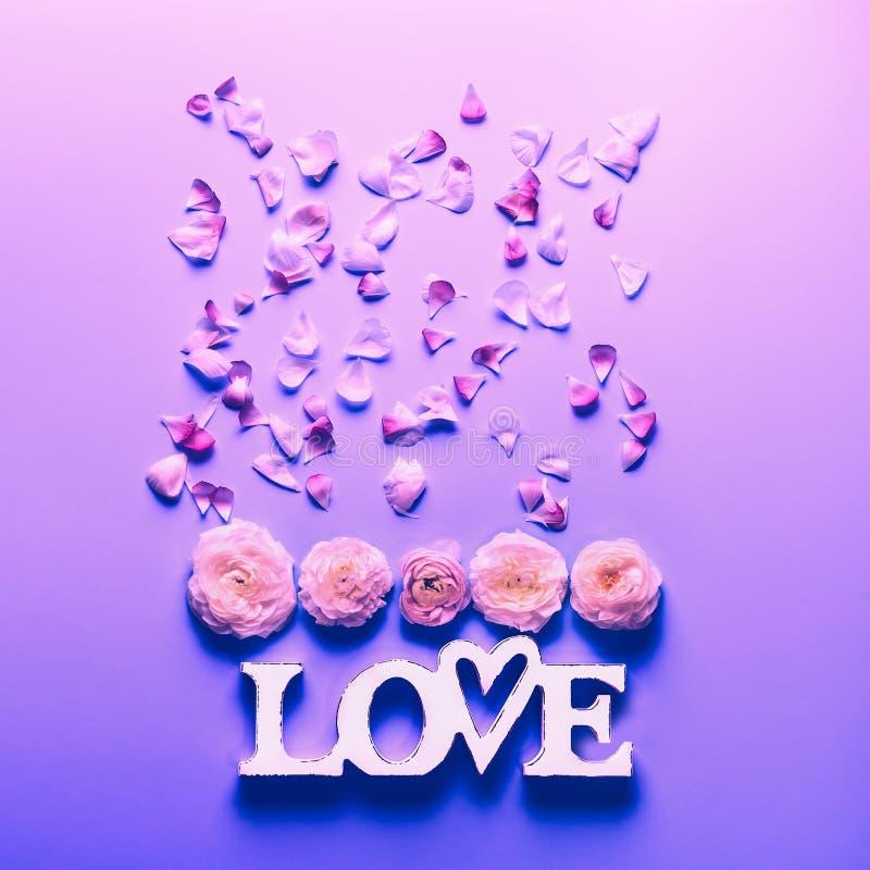 Kwiaty i słowo miłość na neonowym koloru tle Świąteczny kwiecisty pojęcie, odgórny widok Mieszkanie nieatutowy zdjęcie stock