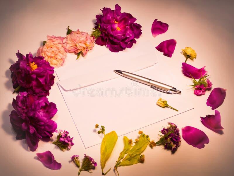 Kwiaty, koperta i pióro na czerwieni, zdjęcia stock