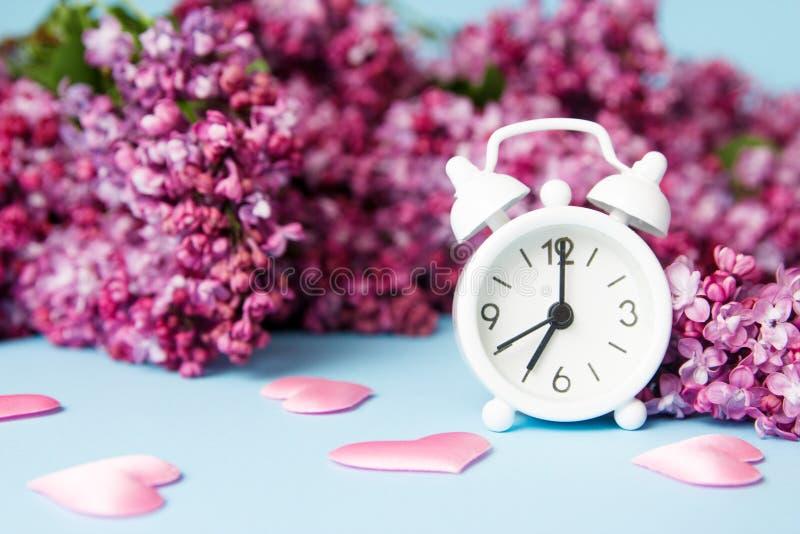 Kwiaty Lilac z budzikiem na niebieskim tle Koncepcja porannej wiosny zdjęcie royalty free