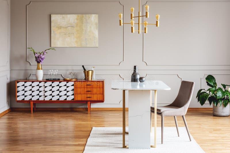 Kwiaty na drewnianej spiżarni w popielatym loft wnętrzu z krzesłem przy stołowym i złocistym obrazem Istna fotografia zdjęcie stock