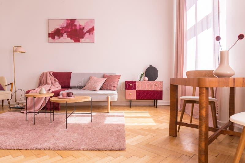 Kwiaty na drewnianym stole w różowym mieszkania wnętrzu z kanapą pod plakatem obok gabineta Istna fotografia obrazy stock