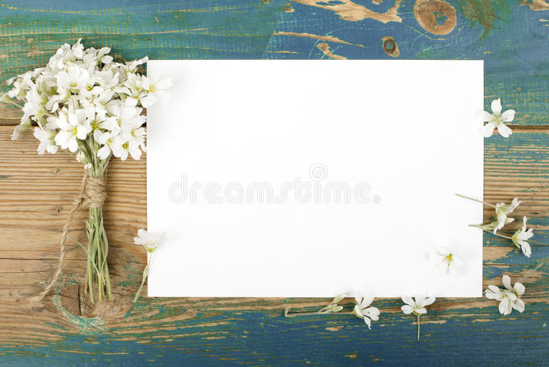 Kwiaty na rocznik drewnianych deskach z pustym papierem obraz royalty free