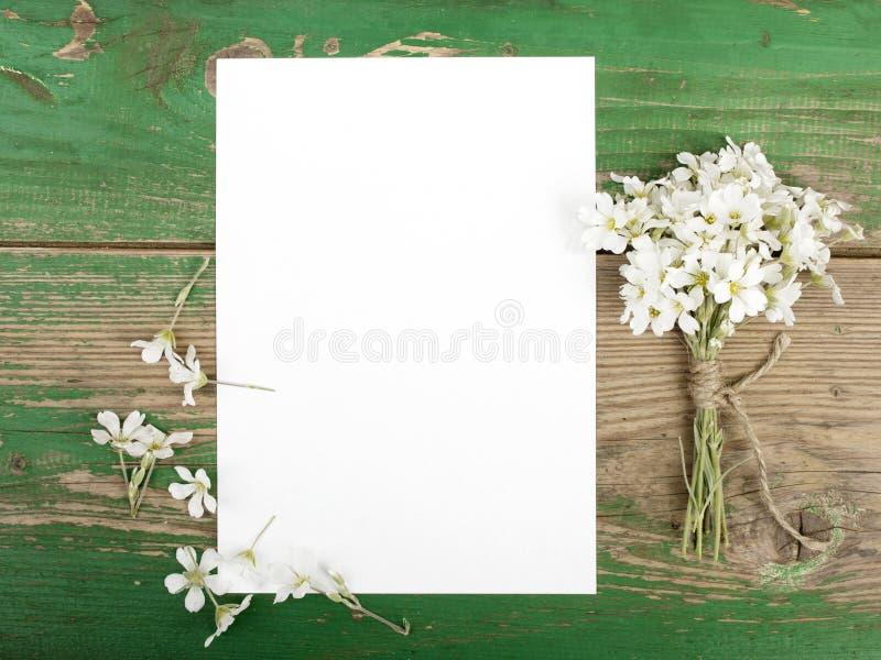 Kwiaty na rocznik drewnianych deskach z pustym papierem fotografia stock