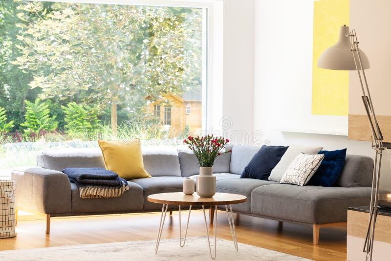Kwiaty na stole obok popielatej narożnikowej kanapy z poduszkami w mieszkania wnętrzu z okno Istna fotografia obraz royalty free
