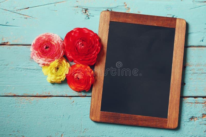 Kwiaty obok pustego blackboard obraz stock