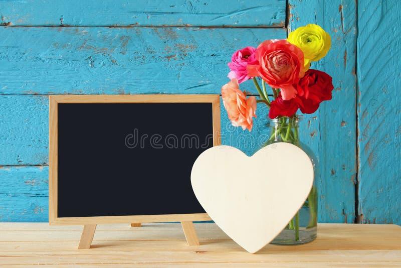 Kwiaty obok pustego blackboard na drewnianym stole, kosmos kopii obraz stock