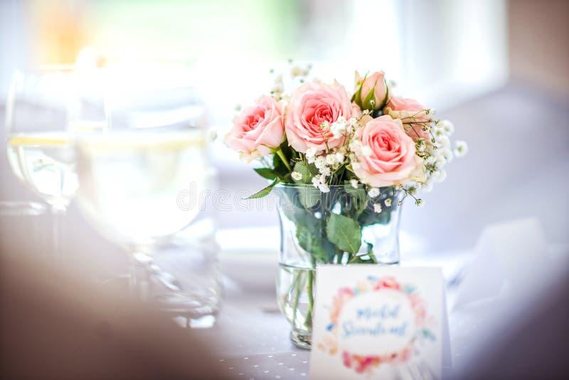 Kwiaty róże na ślubu stole z kartą, romantycznym różowym tle dla przyjęcia lub wydarzeniu, obraz royalty free