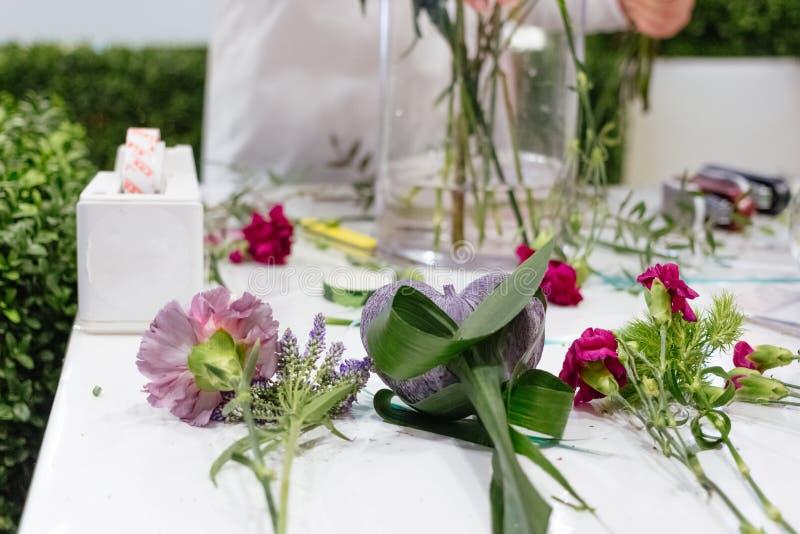 Kwiaty w florystyka kwiatu sklepie kłaść na stole z szklaną wazą obraz stock