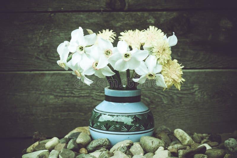 Kwiaty w starej wazie Dandelions i daffodils zdjęcia stock
