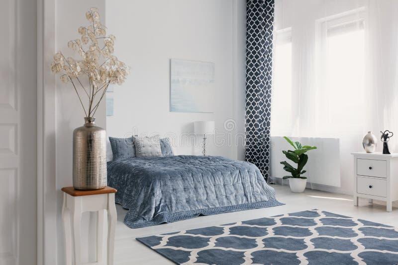 Kwiaty w złocistej wazie w białym sypialni wnętrzu z wzorzystym dywanem przed błękitnym łóżkiem Istna fotografia obraz royalty free