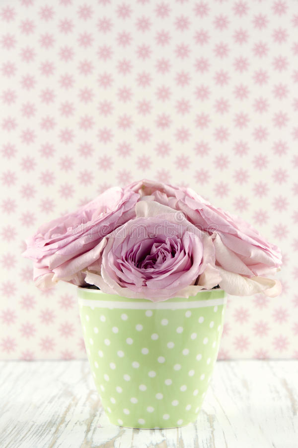 Kwiaty w zielonej polkadot wazie na rocznika drewnianym tle fotografia royalty free