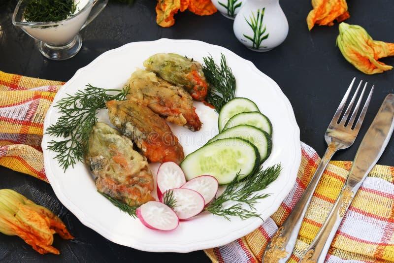Kwiaty zucchini, gotujący w cieście naleśnikowym, plasterkach ogórki i rzodkwiach na talerzu, obrazy stock