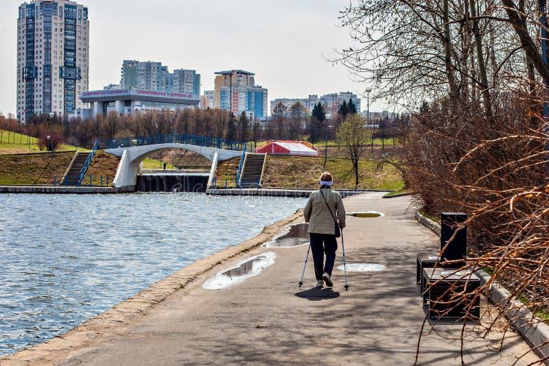 19 Kwiecień, 2018 - Moskwa miasta park Szczęśliwa starsza kobieta angażował w Północnym odprowadzeniu w naturze zdjęcia stock