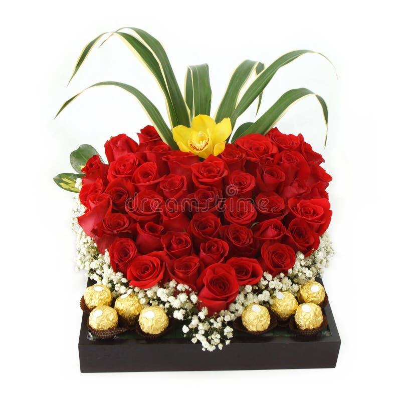 Kwiecisty prezenta przygotowania robić z czerwonymi różami z czekoladami wśrodku drewnianego garnka obraz royalty free