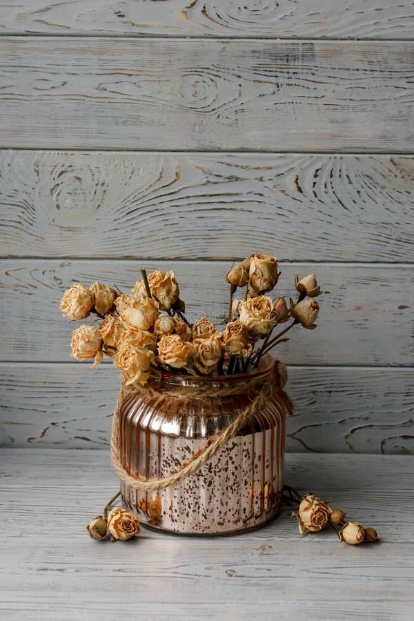 Kwiecisty skład menchie naciskał róże w brąz wazowej pozyci na drewnianej desce Wciąż życie kwiecisty skład na stole Jest obraz royalty free