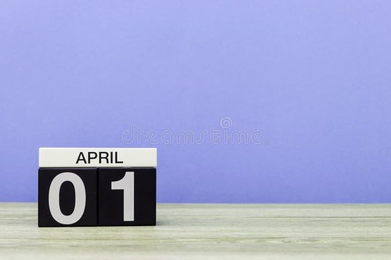 Kwietnia 1st dzień 1 miesiąc, kalendarz na drewnianym stole i purpury tło, Wiosna czas, opróżnia przestrzeń dla teksta zdjęcie royalty free