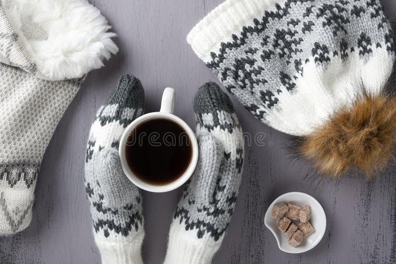 Kwikbreiwerk: mittens, hoed, sjaal en kop koffie op een grijze rustige houtachtergrond Winterkozy nog leven Bovenaanzicht stock fotografie