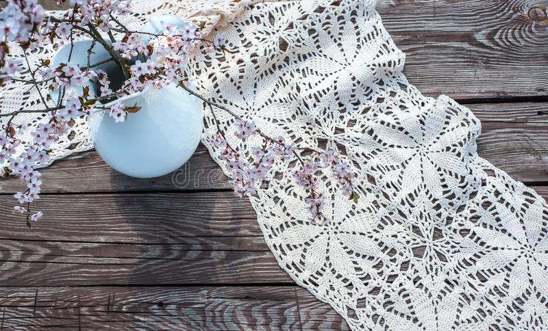 Kwitnący chery sprigs w białym vaze z lazurowym tablecloth na starzejącym się brązu sosnowym drewnie fotografia royalty free