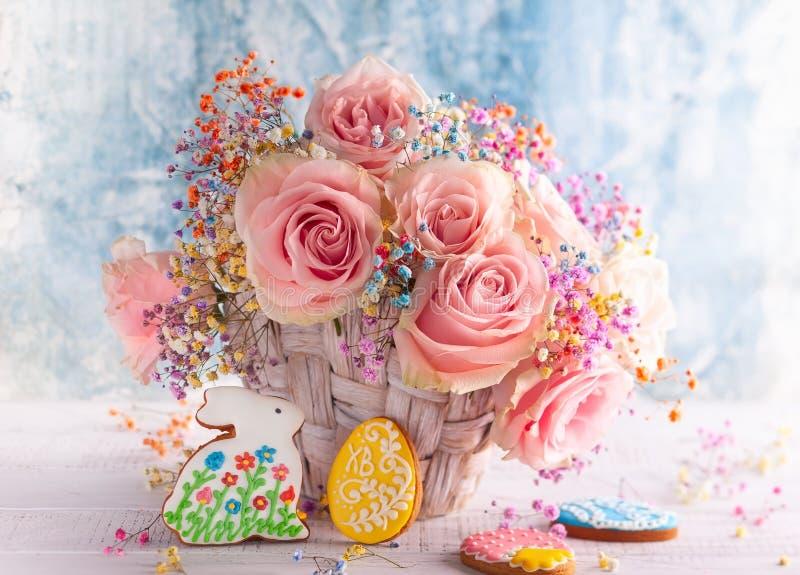 Kwitnie skład z pastelowymi różami i Wielkanocnymi ciastkami dla wakacje zdjęcia royalty free
