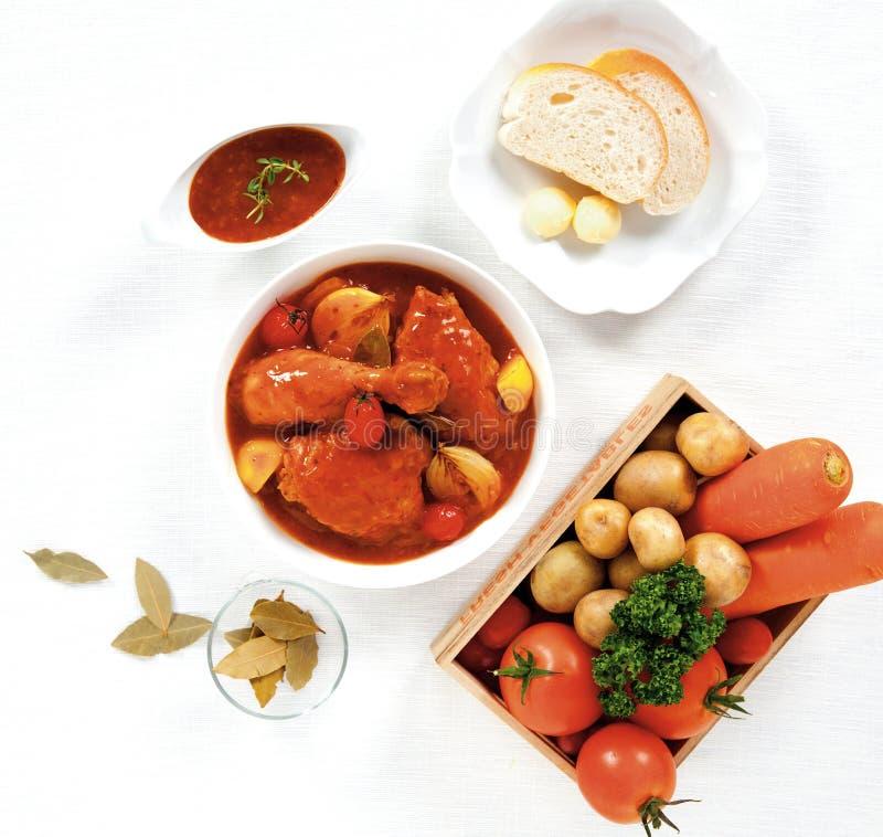 Kycklinggrytan och bröd med smör i den vita bunken, grönsak i en träask satte ner beside på den vita tabellen, bästa sikt royaltyfria bilder