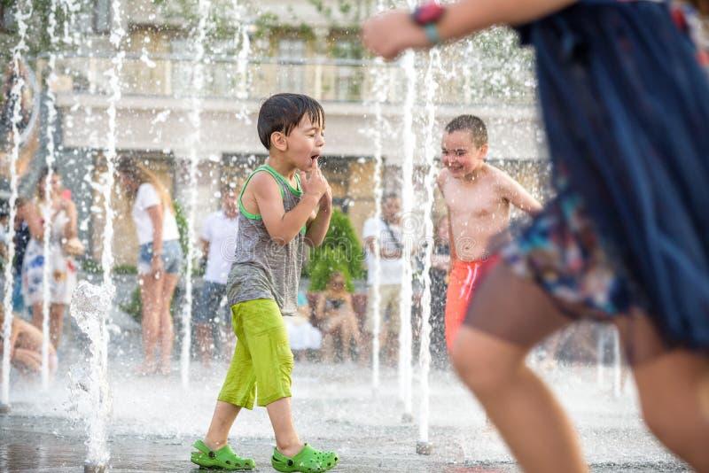 KYIV,乌克兰2017年8月13日:愉快的孩子获得使用的乐趣在城市给水喷泉在热的夏日 图库摄影