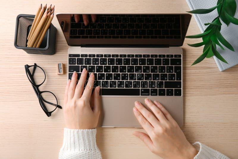 KYIV, DE OEKRAÏNE - OKTOBER 24, 2017: Vrouw die het Goud van Apple gebruiken MacBook bij lijst stock afbeelding