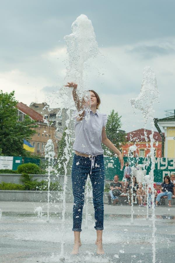 Kyiv MA, 19-07-2018 Nettes Mädchen des jungen jugendlich im Stadtbrunnen, Mädchen in der nass Kleidung hat Spaß und genießt den k stockfoto
