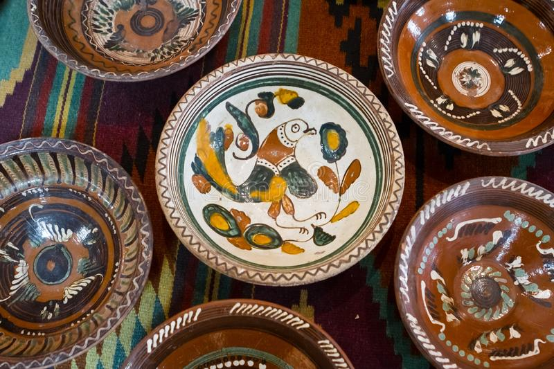 Kyiv-Pechersk Lavra museum, Ukraine - 07.06.2016: ancient Ukrainian handmade and handpainted ceramic clay plates. Fantastic creature pattern, traditional folk royalty free stock images