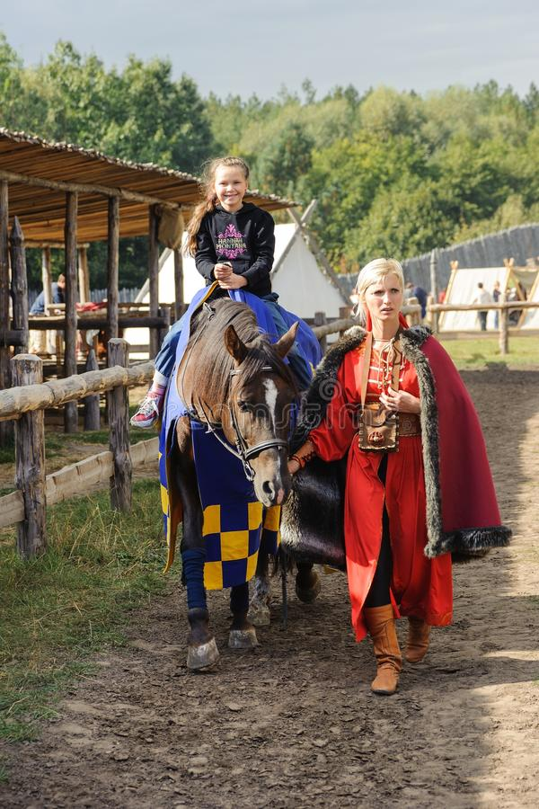 Kyiv region, UA, 24-09-2011, The child sits on a horse, costumed woman helps. Costume Recreation Park Kyivan Rus of medieval perio stock images