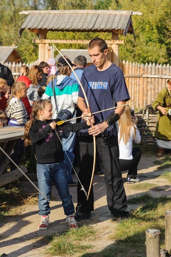 Kyiv region, UA, 24-09-2011. Girl child shoots from the bow, trains the master. royalty free stock image