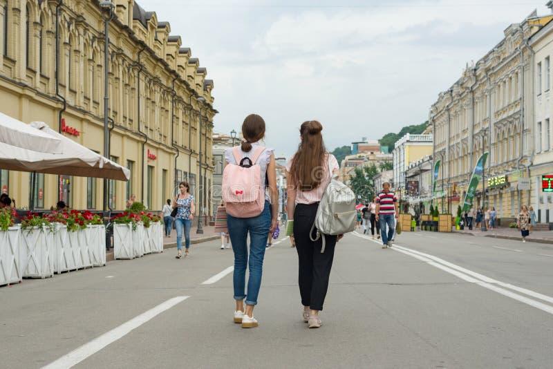 Kyiv UA, 19-07-2018 年轻十几岁的女孩学生通过城市走,从后面的看法的街道 库存照片