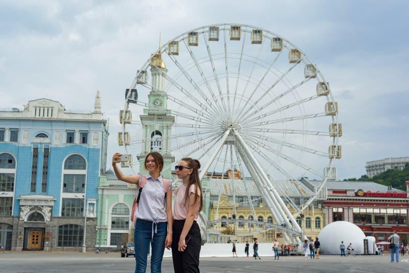 Kyiv UA, 19-07-2018 Европейский город, колесо ferris развлечений на квадрате Туристы маленьких девочек сфотографированы в backgro стоковые изображения