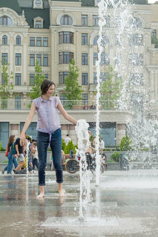 Kyiv UA, 19-07-2018 Den gladlynta unga tonåriga flickan i stadsspringbrunn, flicka i våt kläder har gyckel och tycker om den kall royaltyfri fotografi