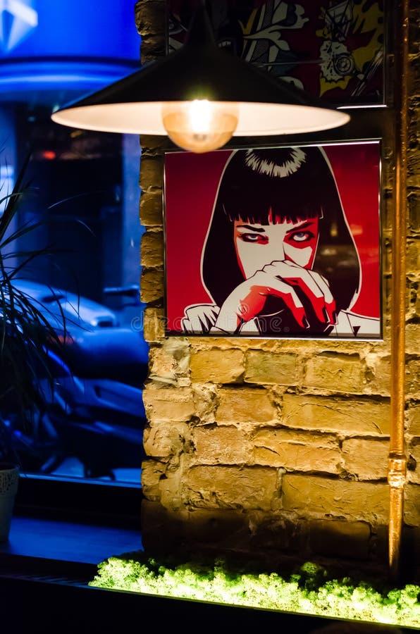 Kyiv, Ucrânia - 10 de junho de 2019 Barra de Warhol Interior da barra Ilustração com a imagem de uma menina em uma parede de tijo fotografia de stock