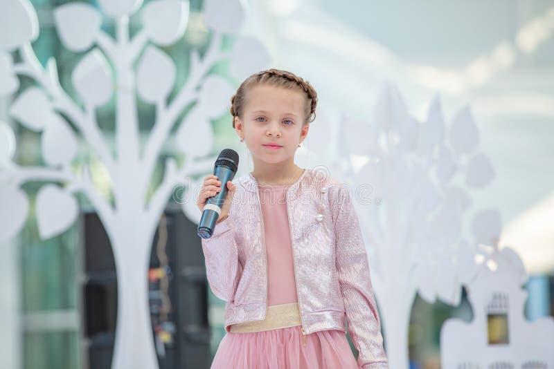 Kyiv, Ucrânia o 3 de março 2019 UKFW As crianças ucranianas formam o dia A menina guarda o microfone em sua mão ao executar a mús imagens de stock royalty free