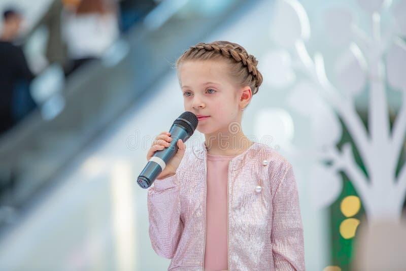 Kyiv, Ucrânia o 3 de março 2019 UKFW As crianças ucranianas formam o dia A menina guarda o microfone em sua mão ao executar a mús foto de stock