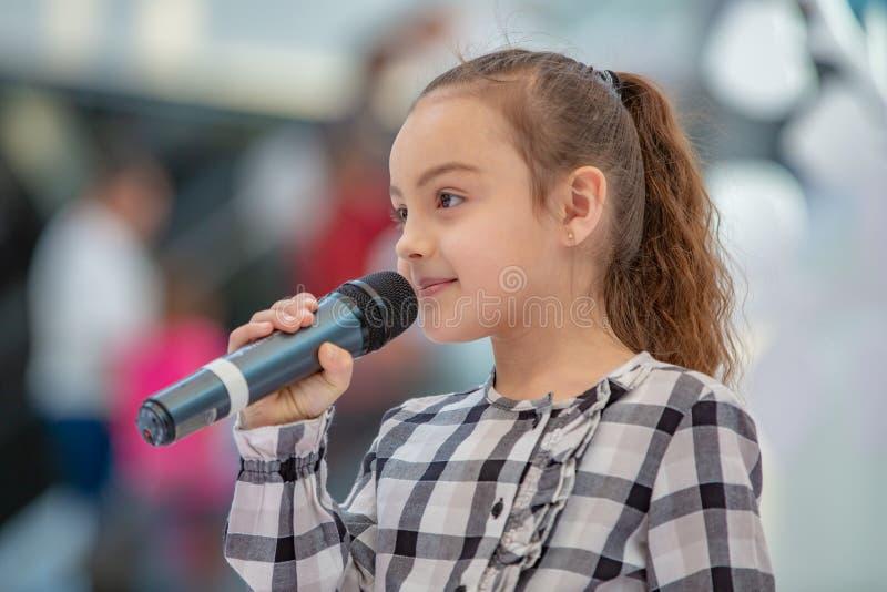 Kyiv, Ucrânia o 3 de março 2019 UKFW As crianças ucranianas formam o dia A menina guarda o microfone em sua mão ao executar a mús imagens de stock