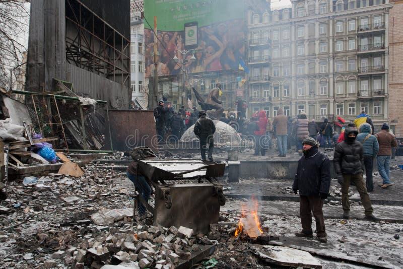 KYIV, UCRÂNIA: O fogo ativo da queimadura dos povos após barricadas após a noite luta na rua destruída do inverno durante o motim imagem de stock