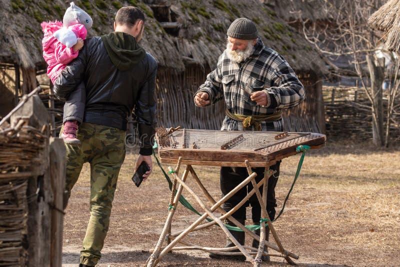 Kyiv UCRÂNIA - 8 DE MARÇO DE 2019: Feira da arte popular em Pirogovo Um avô farpado grisalho na jarda de um tradicional velho fotografia de stock