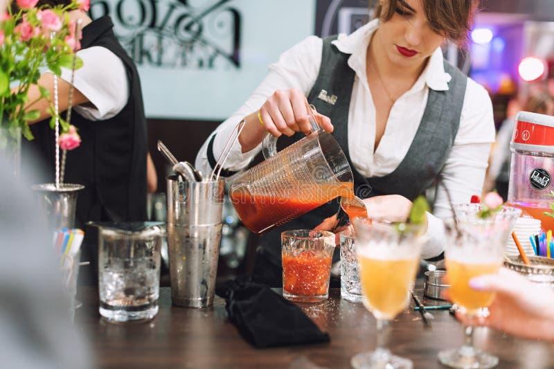 Kyiv, Ucraina - 30 ottobre 2016: Festival del barista Il giovane barista grazioso della donna sta facendo il cocktail fotografia stock