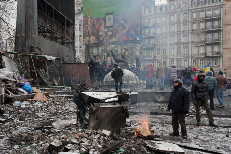 KYIV, UKRAINA: Aktywni ludzie palą ogienia past barykady po nocy walk na zniszczonej zimy ulicie podczas zamieszki obraz stock
