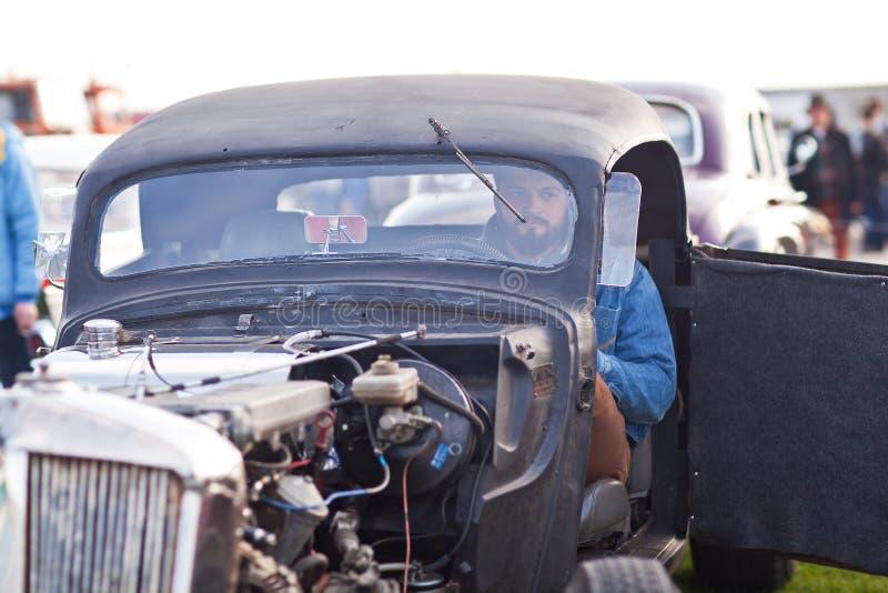 Kyiv Ukraina - 23 APRIL, 2016: Man i gammal amerikansk hotroad på utställningen av gamla bilar - OldCarLand 2016 arkivfoto