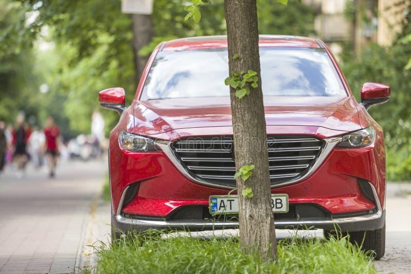 Kyiv Ukraina - Augusti 25, 2018: Bil som parkeras i fot- zon under träd på stadsgatan med att gå folk på sommardag arkivbild