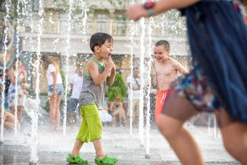 KYIV UKRAINA AUGUSTI 13, 2017: Lyckliga ungar har gyckel som spelar i stadsvattenspringbrunn på varm sommardag arkivbild