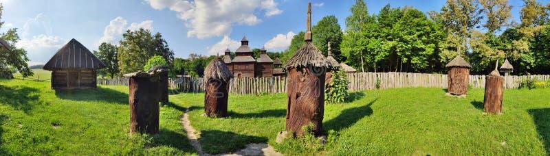 Kyiv Ukraina - Juni 12, 2019: Bibikupor i stammarna av träd Forntida version av bikupan Utomhus- museum av Folk arkitektur arkivbild