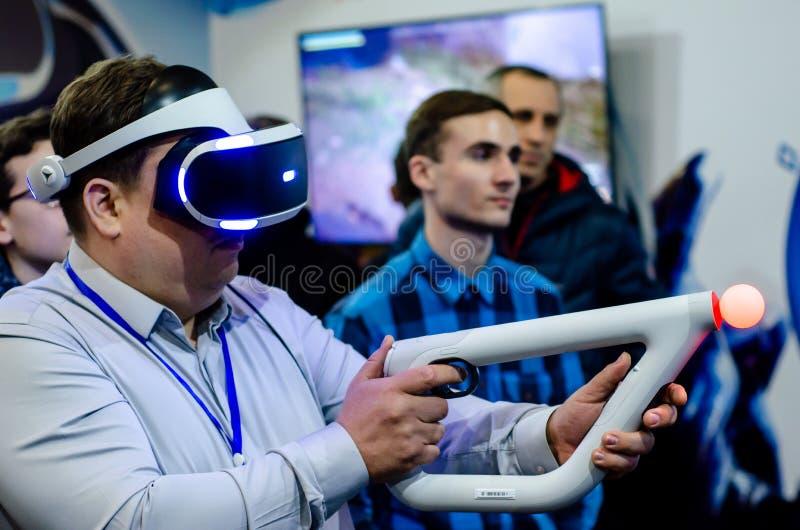 Kyiv Ukraina, Kwiecień, - 12, 2019: Mężczyzna bawić się PlayStation VR z celu kontrolerem fotografia royalty free