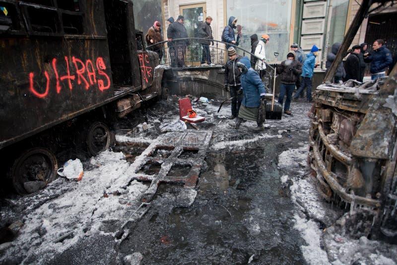 KYIV, UKRAINA: Ludzie chodzą za zimy ulicą z zalodzonymi autobusami palącymi w walkach z milicyjnymi oddziałami podczas zamieszki zdjęcia royalty free